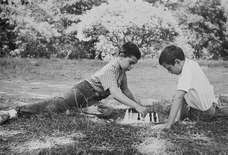 Two boys play chess outside