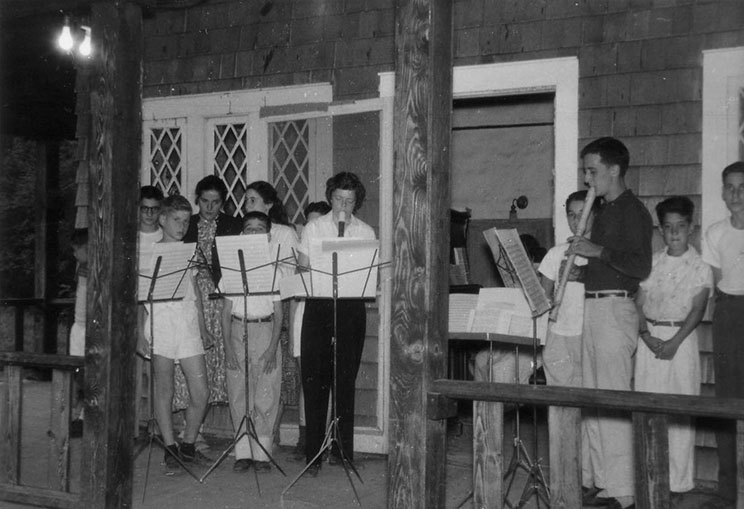 Campers sing outside of a camp building
