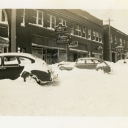 Photo depicts snowy street with vehicles and storefronts of bank, café, Farmers Hardware & Supply Co., and Quality Shoe Shop.